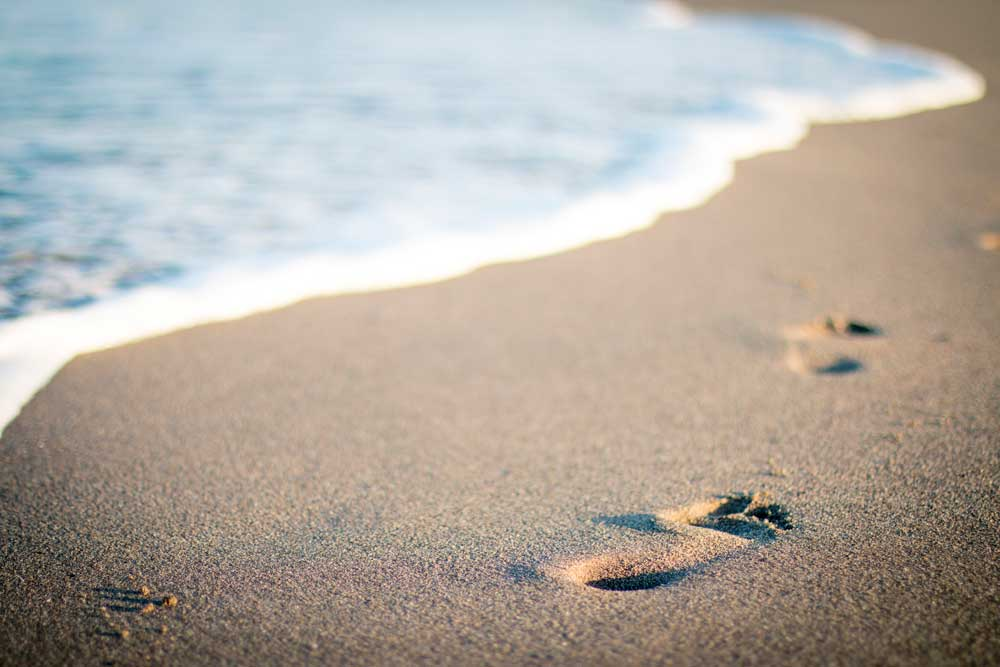 Freedom and Fulfillment - Footprints in sandy beach